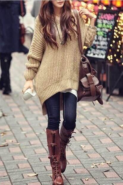 Elegant brunette in dark blue jeans and a beige oversized sweater