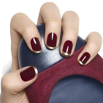 glossy dark red nail polish with metallic gold tips
