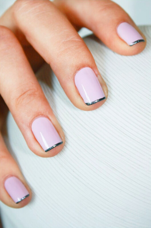 light pink manicure with a thin, straight line of iridescent blue polish on the tips