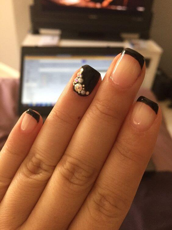 manicure with clear polish and thin, black tips as well as a black accent nail with rhinestone detail