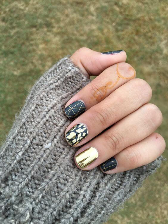 This artistic manicure uses three distinct patterns in black and gold.