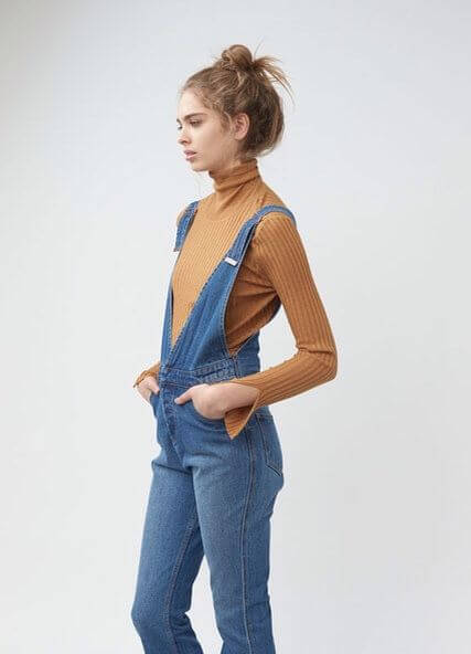 Modestly looking woman wearing a turtleneck top and denim overalls
