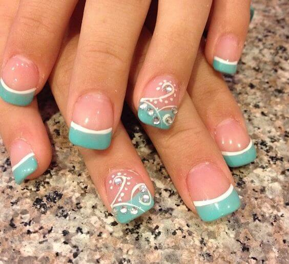nude nail polish with thick, blue-green tips and white spiral and rhinestone designs