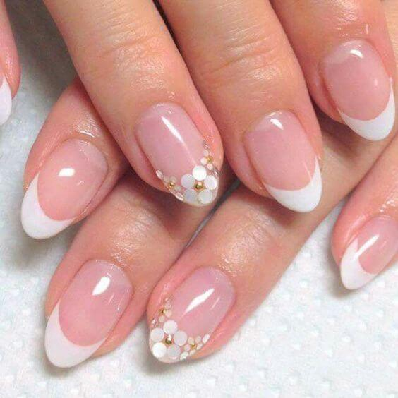 Pink manicure with curved white tips, with the tip on the middle finger made up of small white and gold flowers