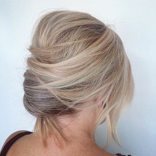 Short blonde French twist hairstyle with bangs and a small bouffant in the back