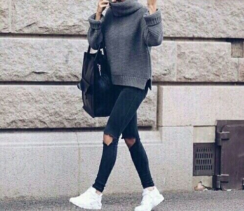 Sporty woman in black denim, white sneakers and an oversized grey sweater