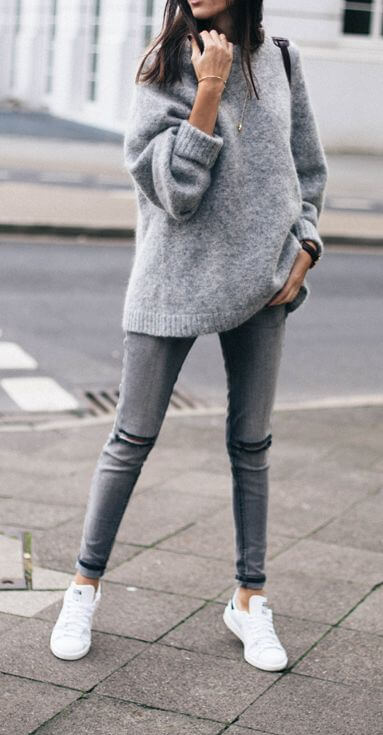 Sporty woman in grey skinny jeans and an oversized grey mohair sweater