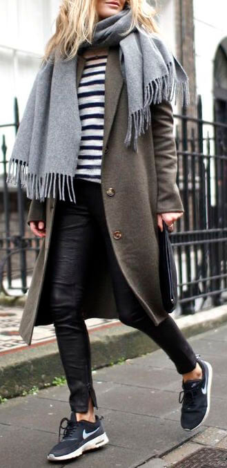 A sporty looking woman wearing black leather leggings, long gray coat and black and white Nike Juvenate sneakers