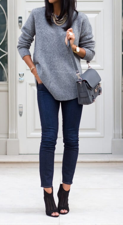 Stylish brunette in blue skinny jeans and a grey oversized sweater