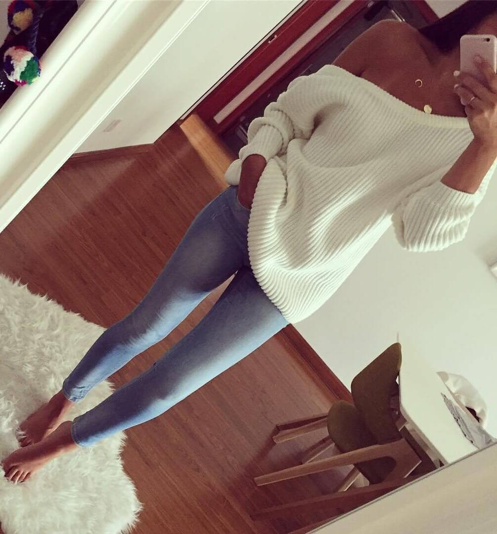 Stylish brunette in blue skinny jeans and cream off-the-shoulder sweater