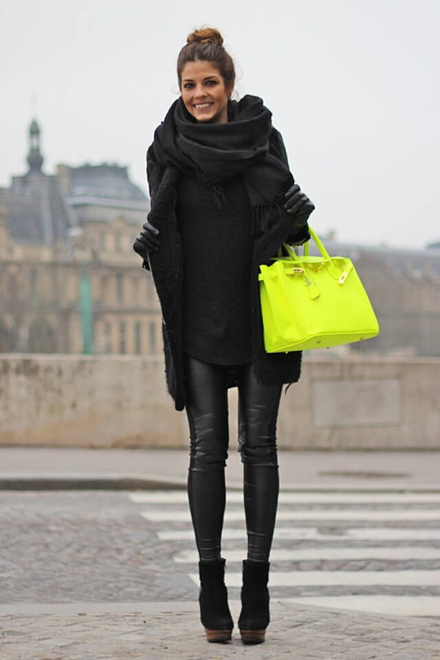 Stylish woman in black leather pants and an oversized black woolen sweater