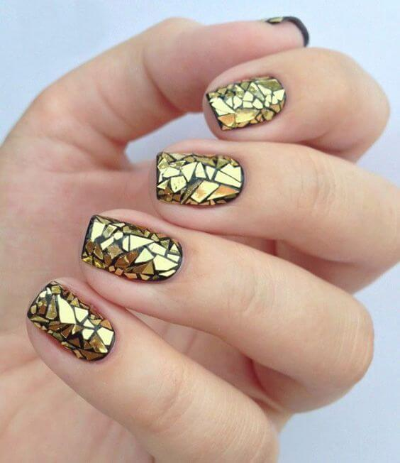 Triangular gold flakes on top of black nail polish