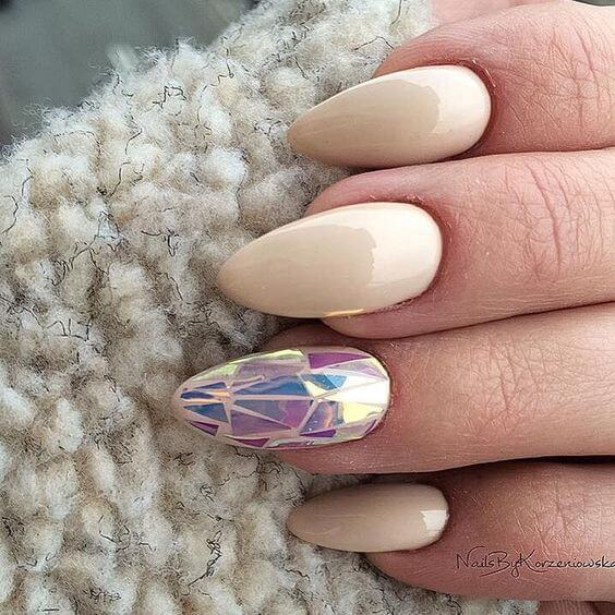 Vanilla manicure with iridescent triangle shapes on the ring finger