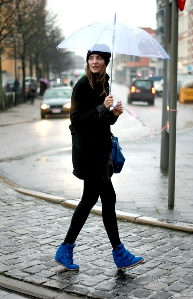 Woman in an all-black look with blue Isabel Marant sneakers