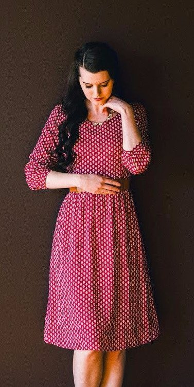 A woman in berry red polka dress looking modest and glamorous at the same time