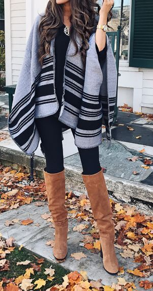 Woman in black leggings, gray poncho and brown boots