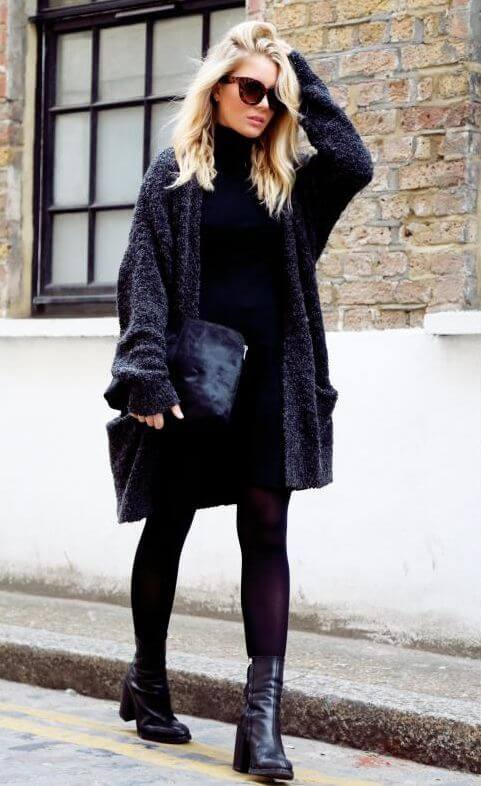 Woman in black tights and long oversized charcoal cardigan