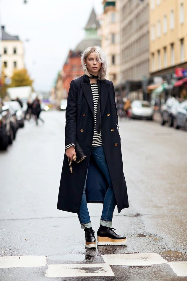 Woman in blue jeans, striped tee, long coat and platform shoes