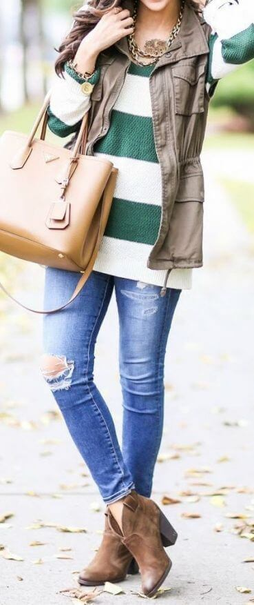 Woman wearing ripped blue skinny jeans, striped sweater, sleeveless khaki parka and brown boots