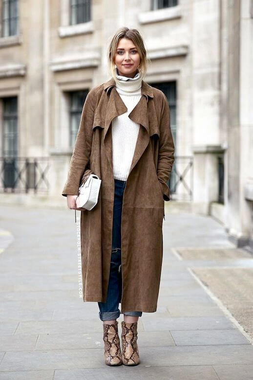 Woman wearing a turtleneck sweater, boyfriend jeans, suede trench and python ankle boots
