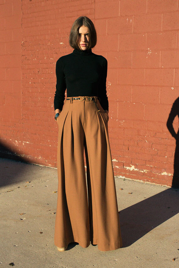 A woman is wearing sandstone palazzo pants and a black turtleneck