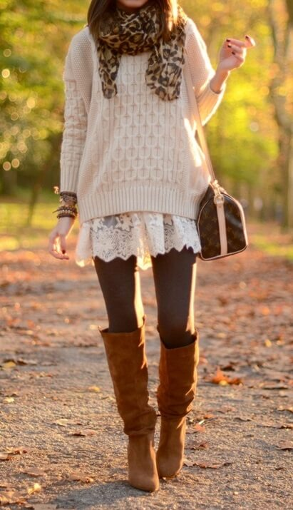 Woman in the park wearing a white lace dress, beige woolen sweater, brown leggings, leopard-print scarf and brown boots