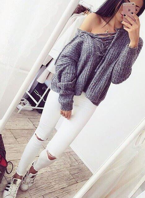 Woman wearing white ripped skinny jeans and oversized gray lace-up sweater
