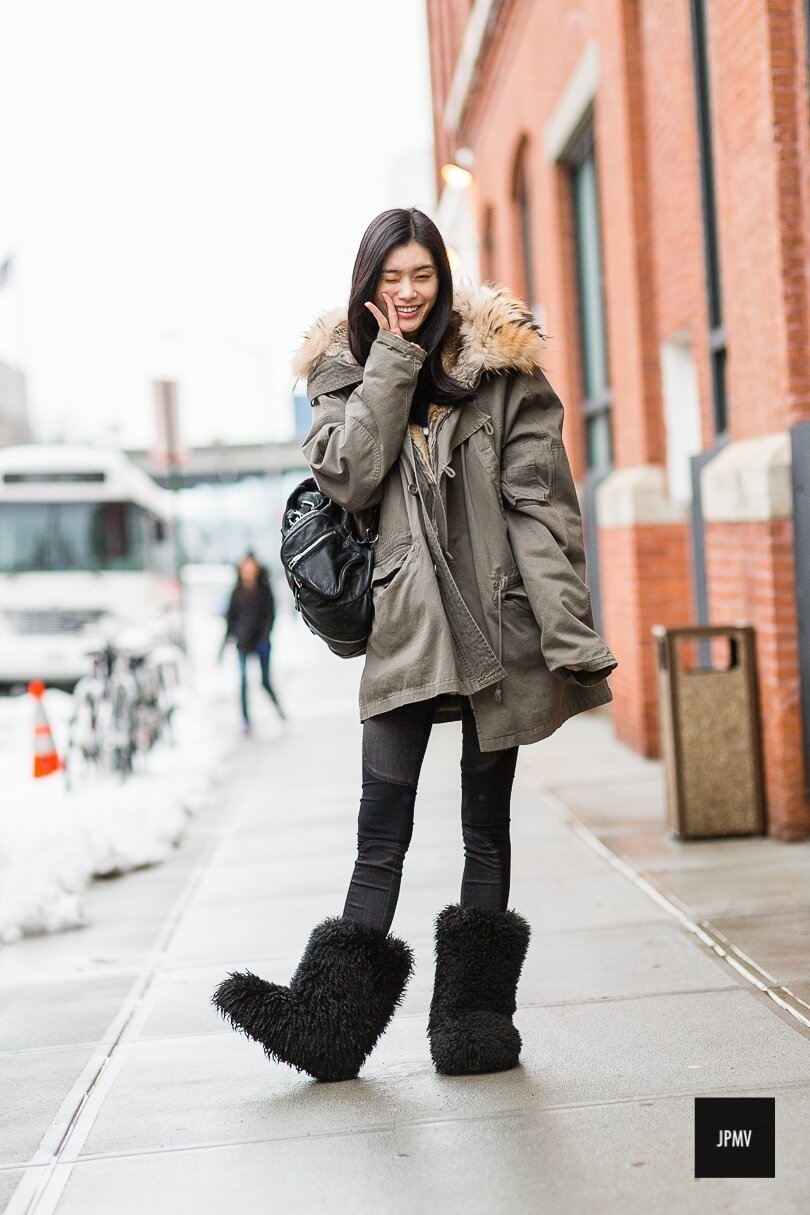 Woman on street wearing skinny jeans with an oversized jacket and fluffy boots