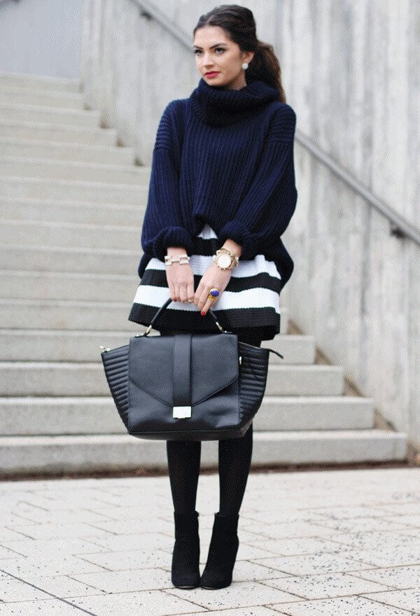 Woman wearing a black and white striped skirt with a blue turtleneck, black leggings, and black booties