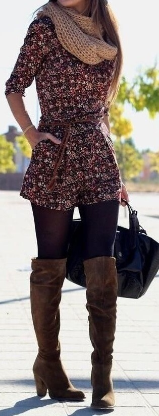 Woman wearing a floral romper, navy blue opaque tights, tan scarf and brown boots