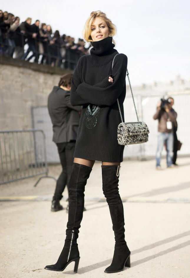 Woman wearing a short black sweater dress with black thigh high boots