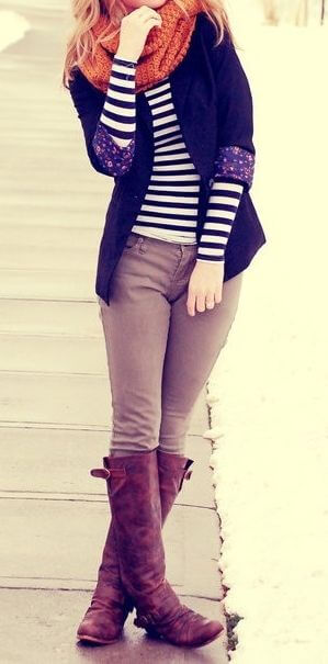 Woman wearing beige pants, striped top, navy blue blazer, orange scarf and brown boots