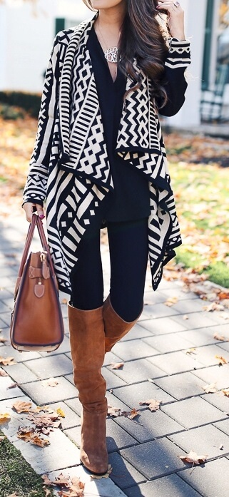 Woman wearing black leggings, long black top, Aztec print poncho, brown leather handbag and brown boots