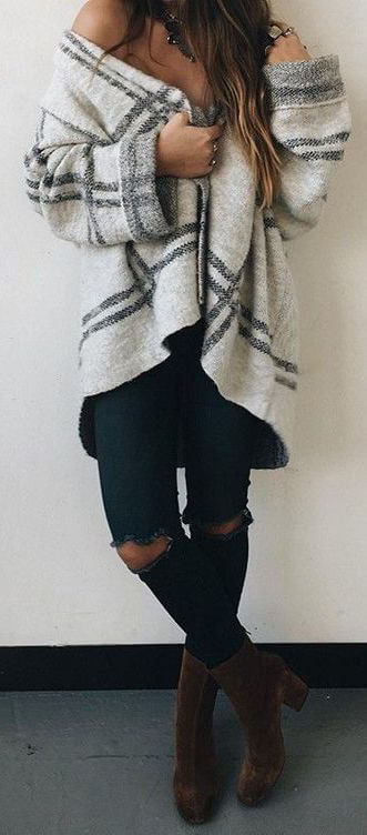 Woman wearing dark blue ripped skinny jeans and gray plaid oversized sweater
