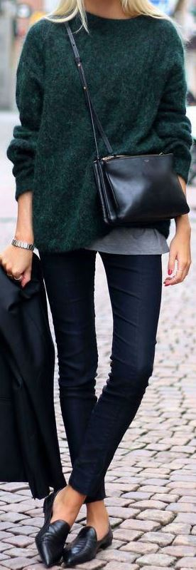 Woman wearing dark blue skinny jeans and olive green sweater