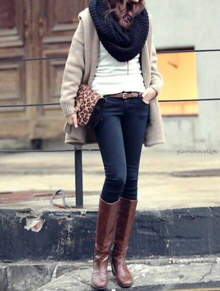 Woman wearing dark blue skinny jeans, white top, beige jacket, navy blue scarf and brown boots with a leopard-print envelope purse