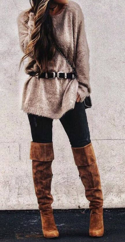 Woman wearing distressed black jeans, a beige oversized wool sweater, black buckle belt and brown boots