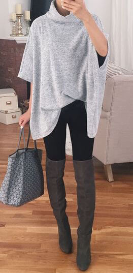 Woman wearing black leggings, dark-gray over-the-knee boots, and gray oversized poncho sweater