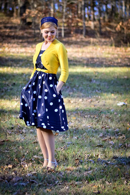A bright look: woman is wearing a navy-blue polka-dotted dress and a yellow cardigan