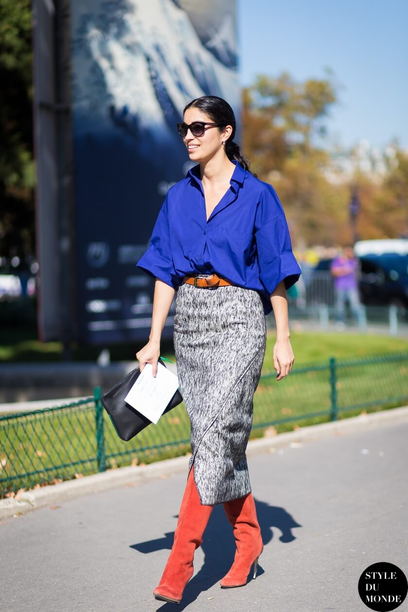 Woman wearing a blue shirt, printed skirt, and red suede boots