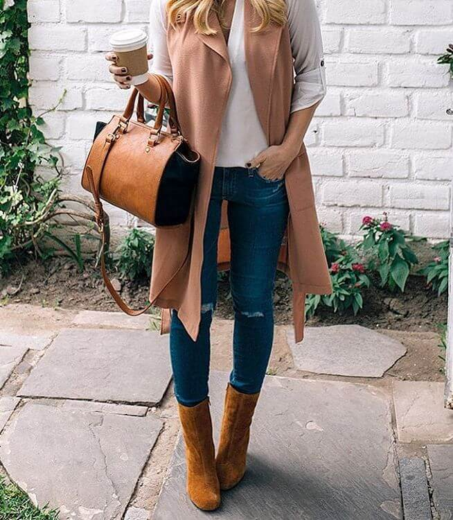 Woman wearing ripped blue jeans, white top, pink sleeveless duster jacket, brown leather handbag and brown boots