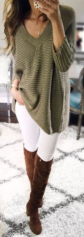 Woman wearing white skinny jeans, oversized olive green sweater and knee-high brown boots