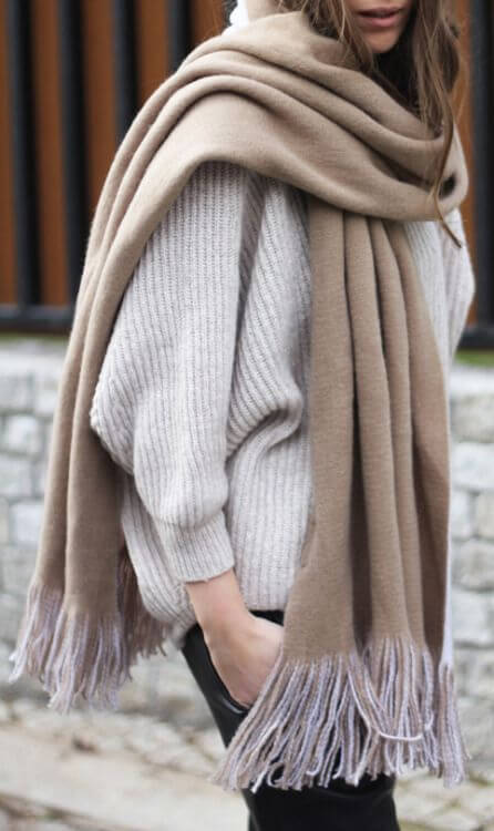 Woman wrapped in sweater and scarf