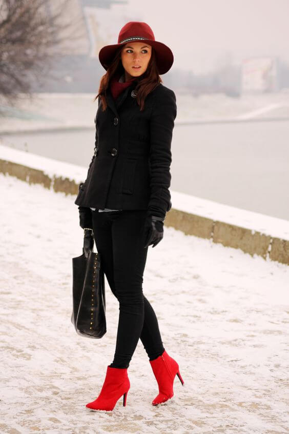 Young woman wearing black pants with a black coat, red boots, and a red hat