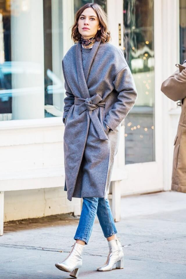 Alexa Chung wearing a wraparound coat, blue jeans, and metallic ankle boots