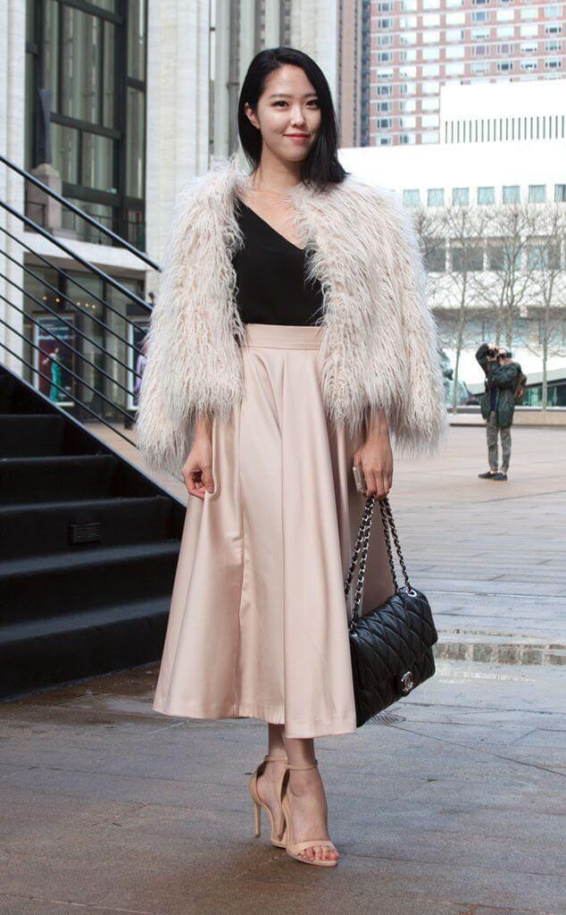 Asian woman wearing a black top with a nude midi skirt, nude heels, and a fluffy coat