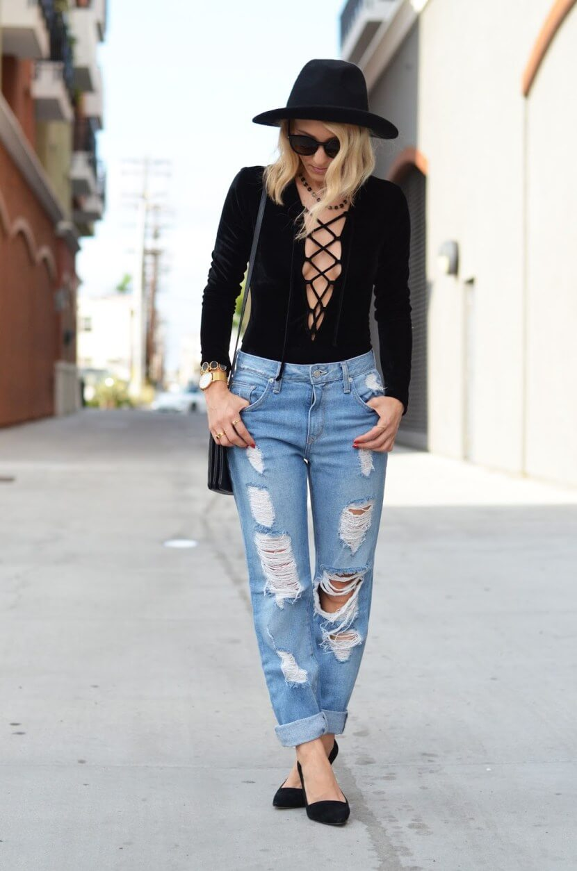 Pretty blonde wearing a black hat, dressed up in lace-up bodysuit and ripped and cuffed boyfriend jeans