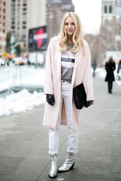 Smiling blonde woman wearing white jeans, silver ankle boots, and a blush pink coat