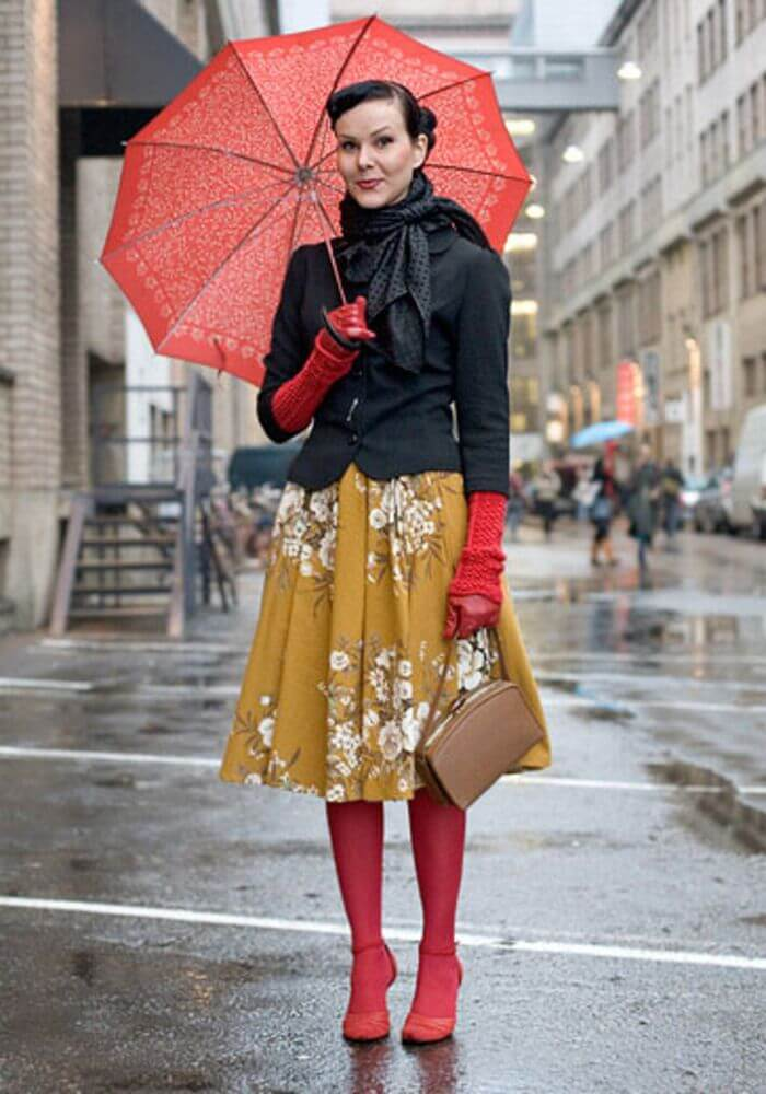 Brunette in a mustard colored printed skirt, with a short black jacket, black scarf, red boots, red gloves, and a red umbrella