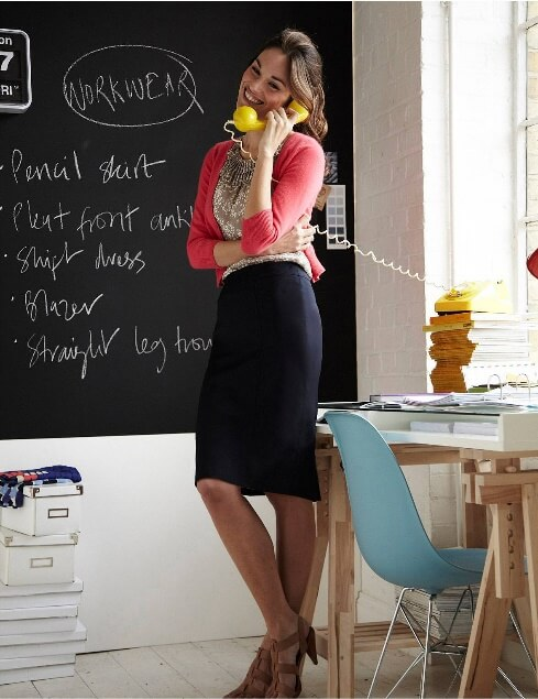 Brunette woman in black woolen pencil skirt and coral cardigan
